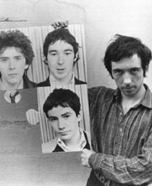 Pete Shelley con le foto dei compagni dei Buzzcocks